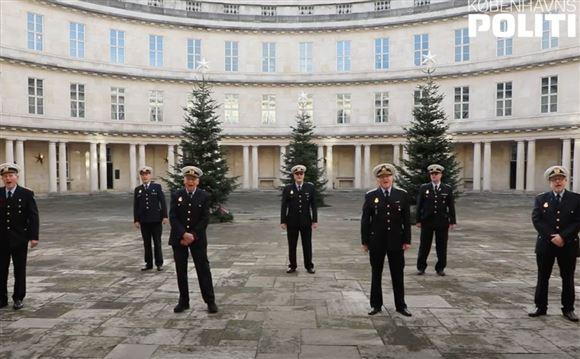 7-8 politimænd står og synger inde i politigården med tre juletræer bagved.