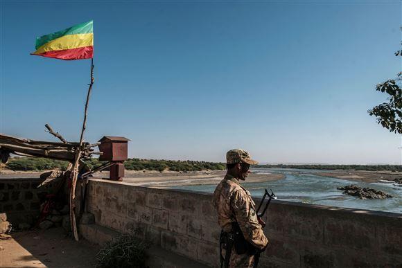 En soldat ved en grænsestation og et slidt etiopisk flag, som vajer i vinden.