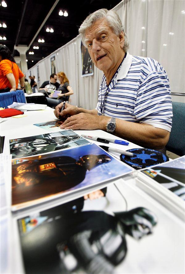 En gråhåret mand i stribet t-shirt signerer billeder