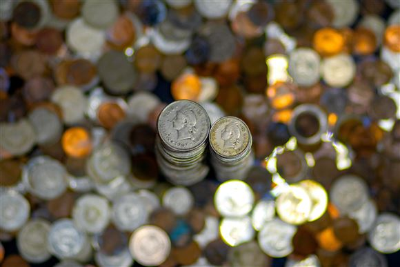 En masse småpenge ligger på et bord. Pengene ses fra oven. Der er også to sirligt stablede tårne af mønter.