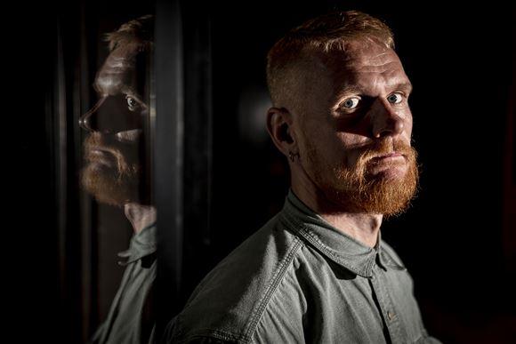 Nærbillede af skuespiller Peter Plaugborg han har stort rødt fuldskæg og et alvorligt blik.