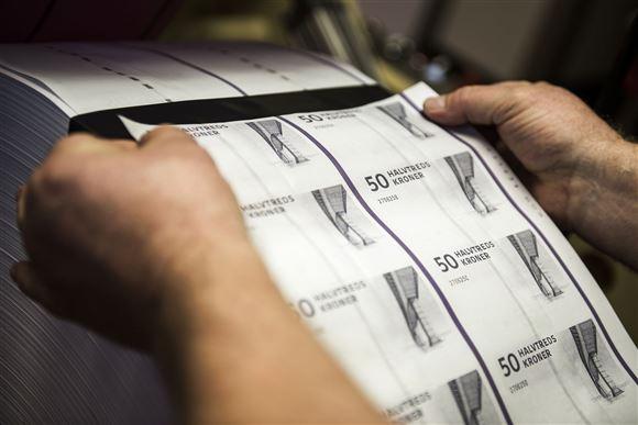 Et sæt hænder står med et ark med halvtredskrone seddler.