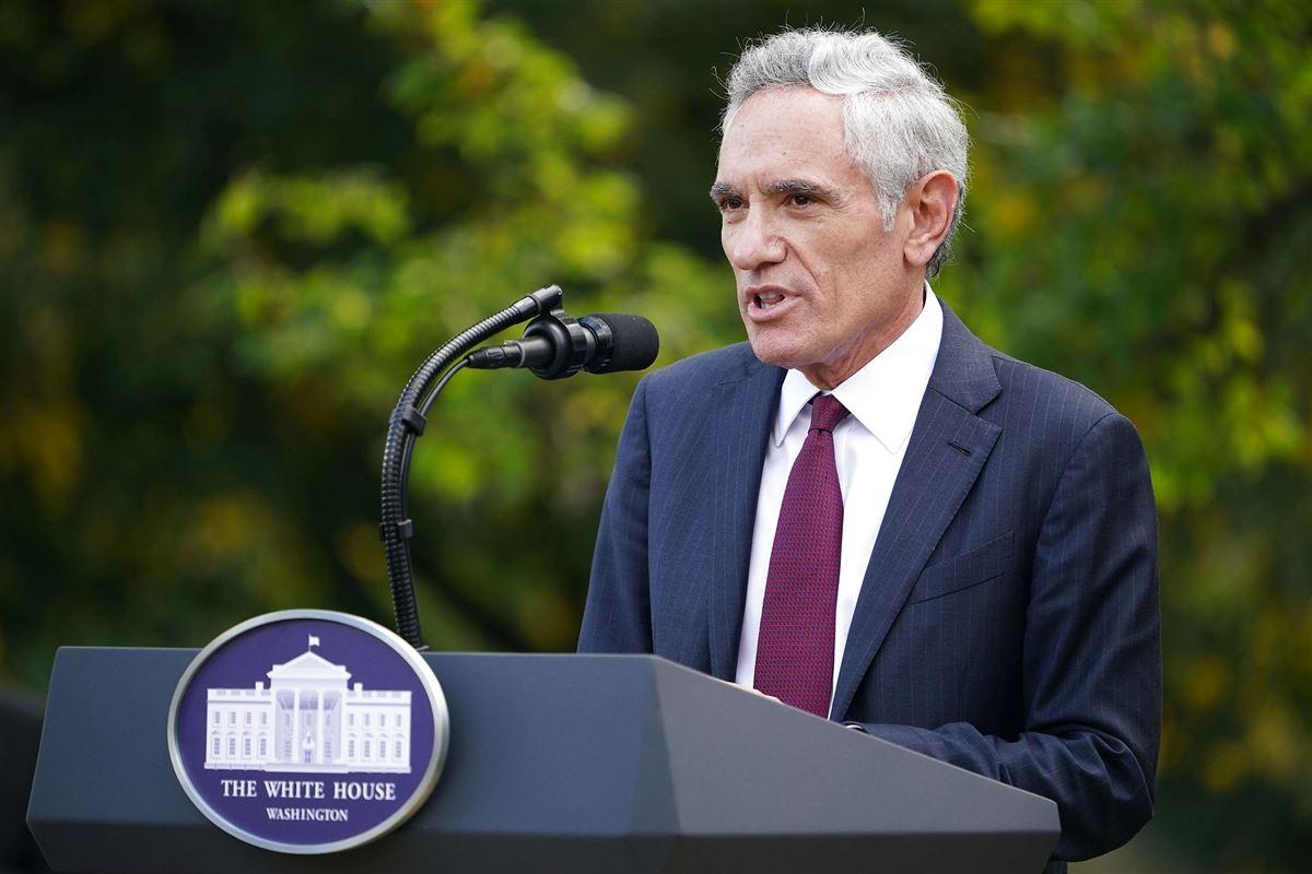 En gråhåret man i nålestribet jakkesæt på en talerstol.
