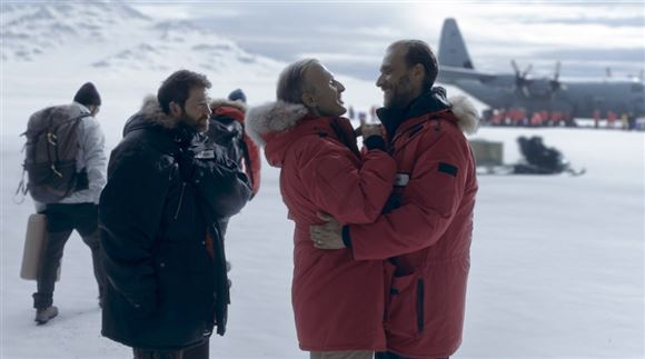 to personer i røde jakker omfavner hinanden på Sydpolen