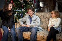 Tre børn i en sofa med juletræ bagved