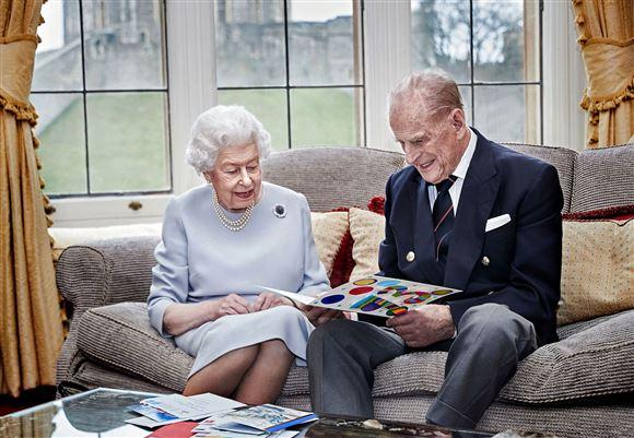 Det engelske regentpar ser billeder i en sofa
