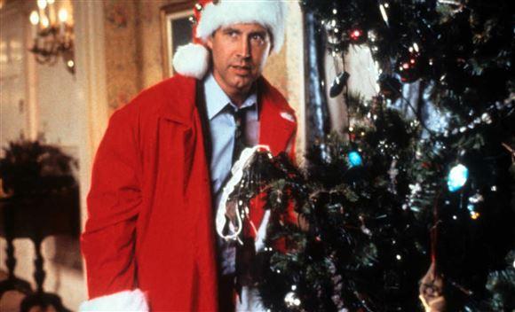 Chevy Chase i julemandsdragt foran træet fra filmen Fars fede Juleferie
