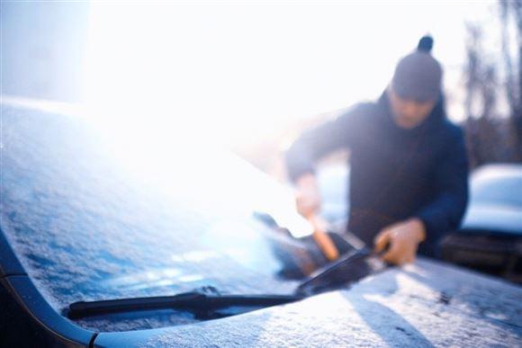 mand skraber frost af bilrude
