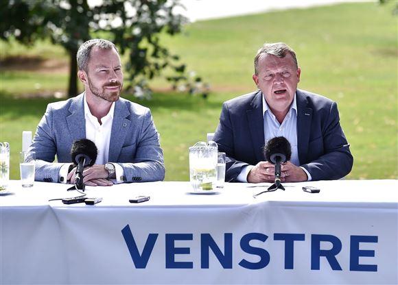 Jakob Ellemann-Jensen og Lars Løkke Rasmussen sidder udenfor ved et bord med mikrofoner