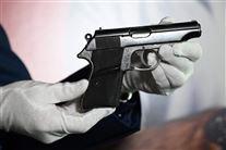 En lille pistol holdt af en mand med hvide handsker