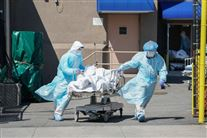 To sundhedsarbejdere trækker af sted med en seng med en patient
