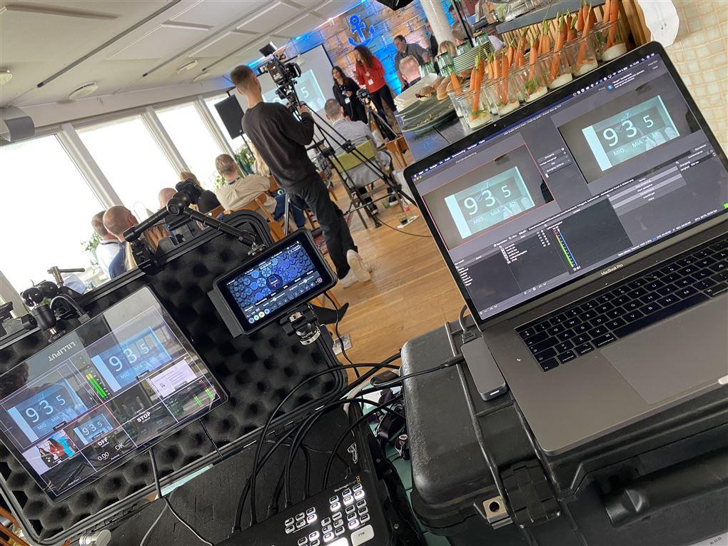 Nogle computere og folk med videokameraer i baggrunden i en sal med folk