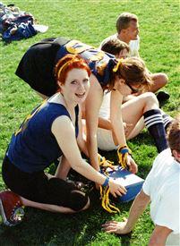 En rødhåret pige sammen med nogle veninder på en græsplæne