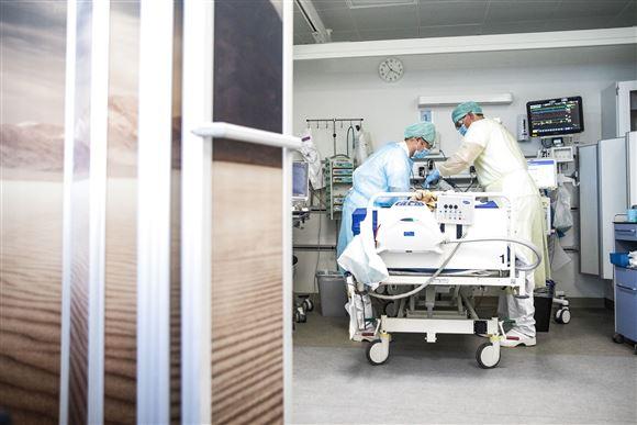 Sygeplejersker tilser patient på hospitalsstue