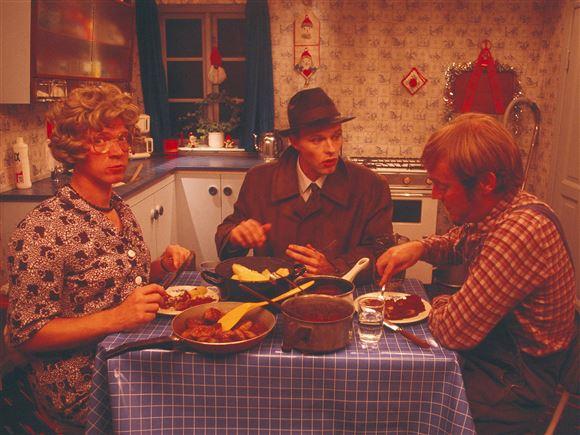 De tre hovedpersoner sidder omkring køkkenbordet