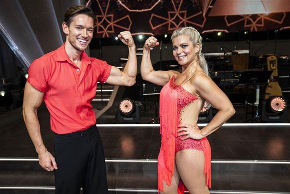 Sara Bro og Morten Kjeldgaard i rødt outfit viser muskler