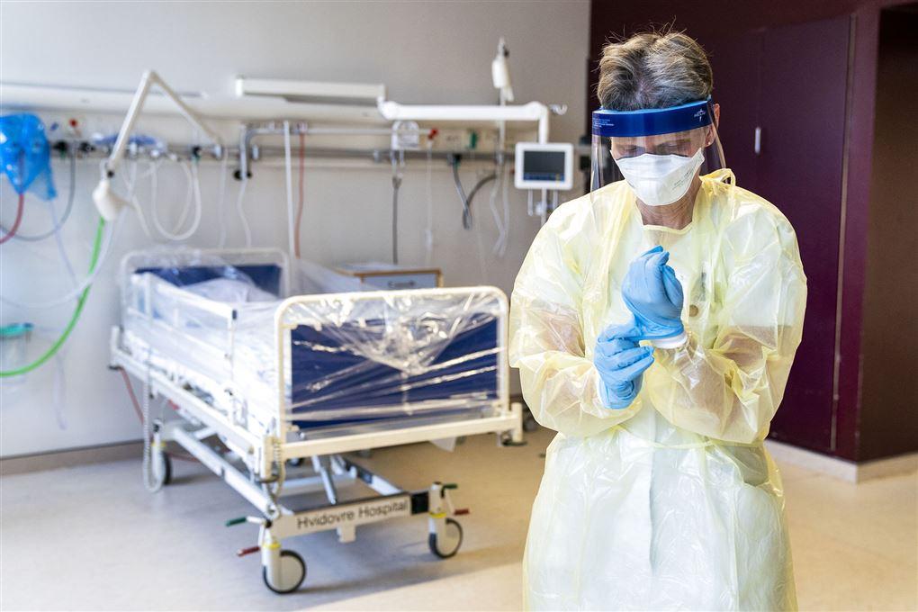 sygeplejerske med handsker og maske står foran tom hospitalsseng