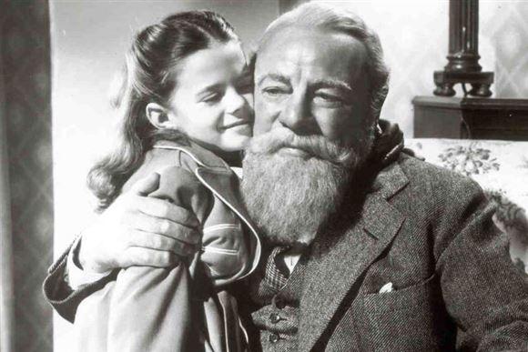 en lille pige krammer en ældre mand med fuldskæg