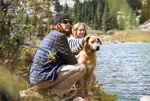 Et par med en hund sidder ved en sø