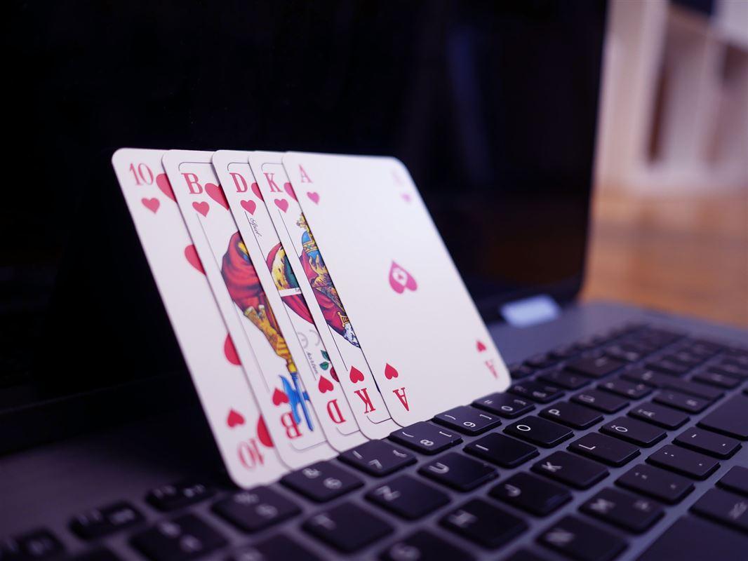 Fem spillekort, der læner sig op af en åben pc