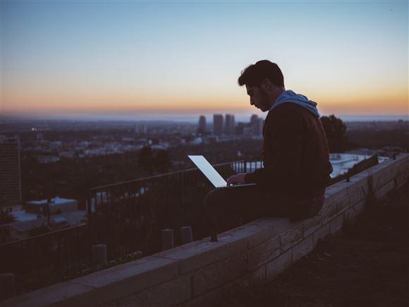 En mand sidder på kanten af et tag med sin åbne pc i skødet i solnedgangen