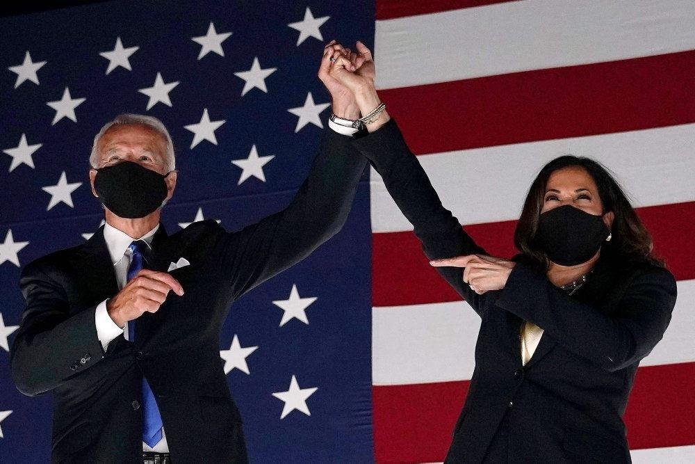 Joe Biden og Kamela Harris står med mundbind og armen i vejret