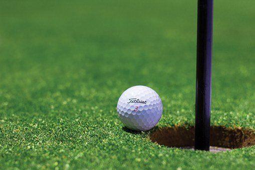Golfbold ligger på hulkanten