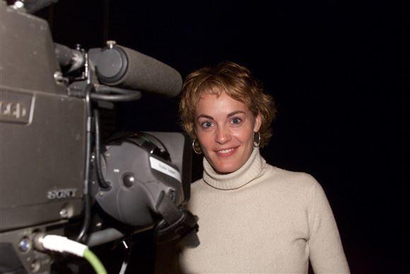 Anja Steensig i højhalset sweater står ved siden af tv-kamera