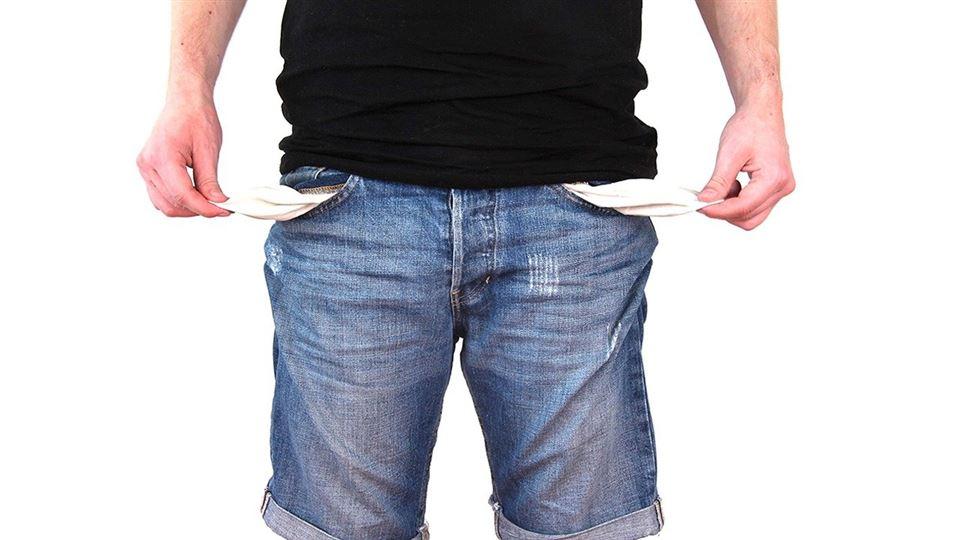 En mand i jeans vender foret ud på sine lommer