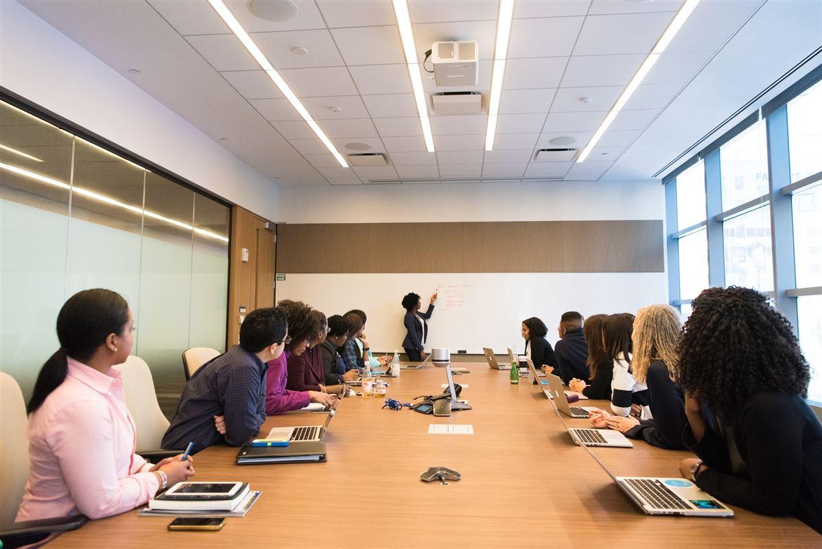 En underviser og mange folk omkring et stort bord