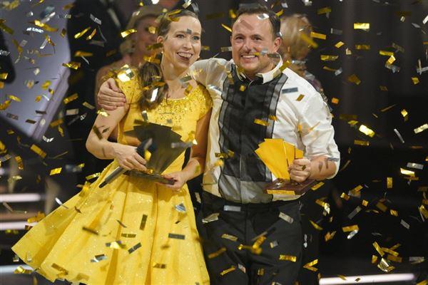 En regn af guldkonfette over de to vindere med trofæer i hændernen