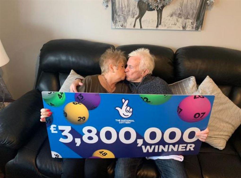 Et ægtepar i en sofa kysser hinanden
