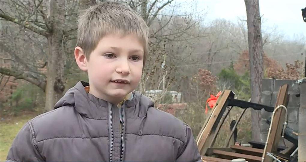 en dreng i dynejakke står foran nedbrændt hus