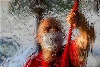 En rude med vand og en mand med skraber bagved