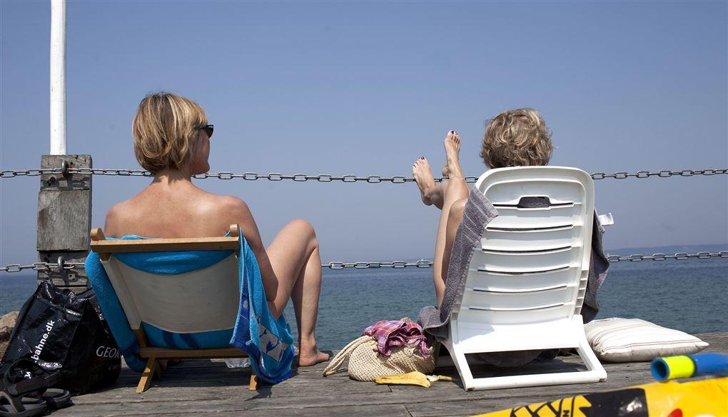 To kvinder med ryggen til sidder i klapstole og kigger ud over havet.