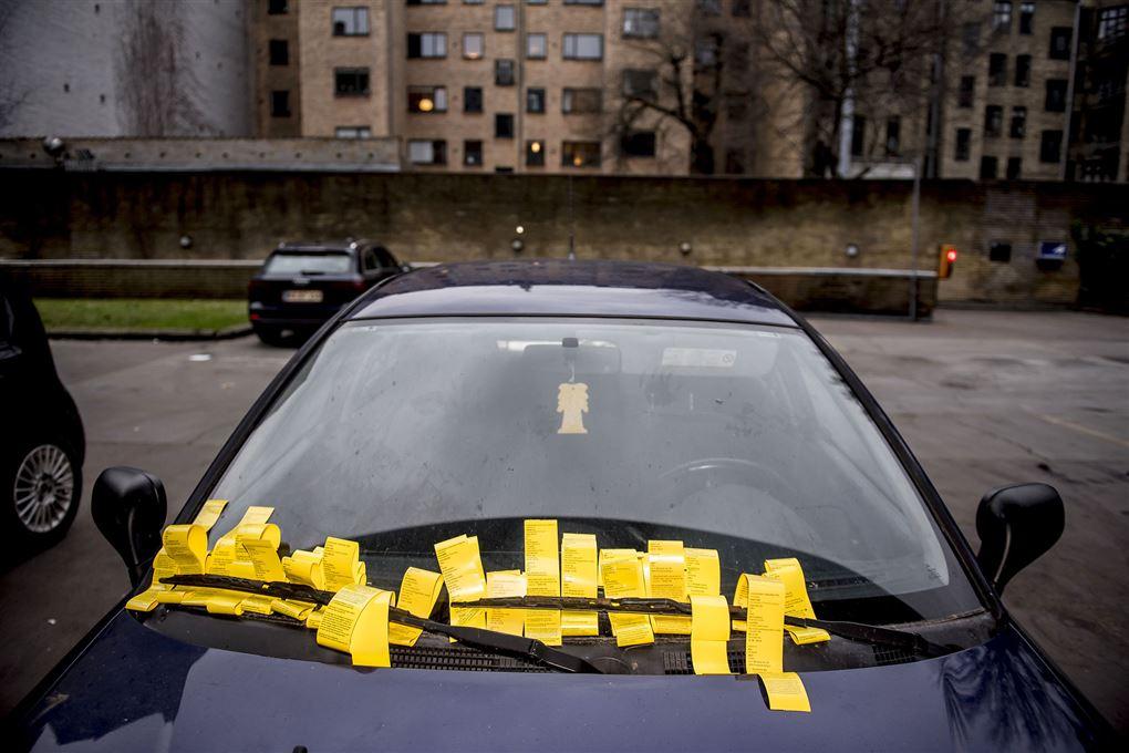 En sort bil med virkelig mange gule parkeringsbøder i forruden.
