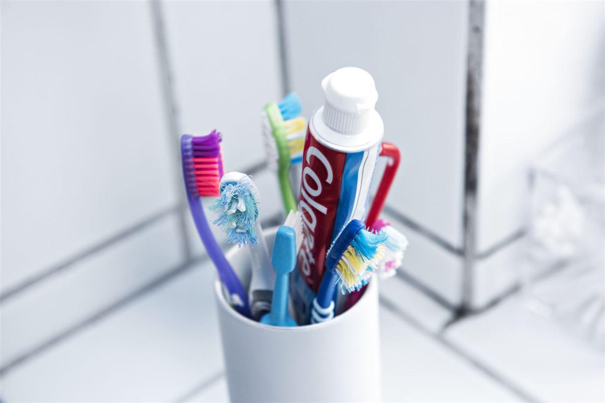 Et glas med forskellige tandbørster og en tube tandpasta.