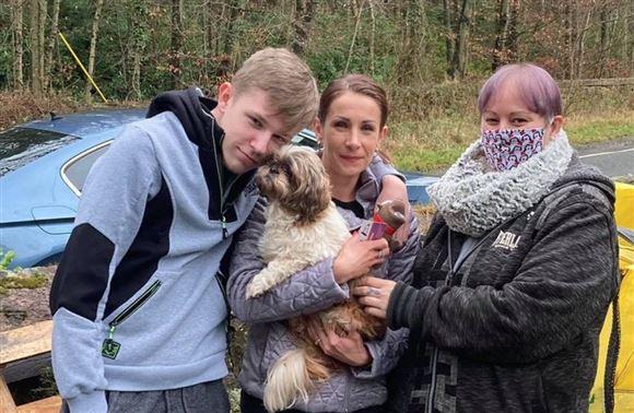 En lille hund i favnen på en kvinde og en ung mand og en kvinde flankerer dem