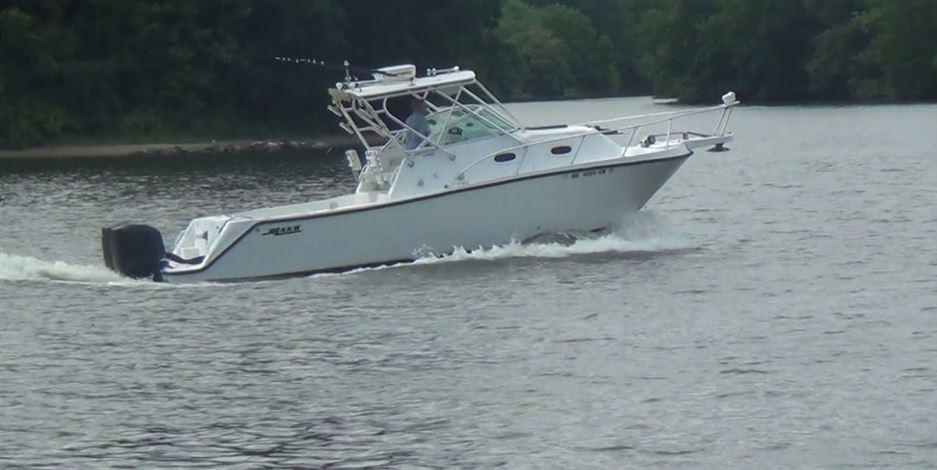 En hvid motorbåd med lille kahyt og udendørs motor.