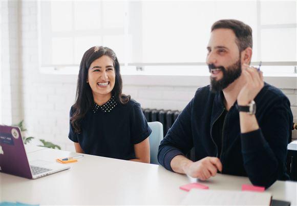 En smilende kvinde som ser på en mand med fuldskæg