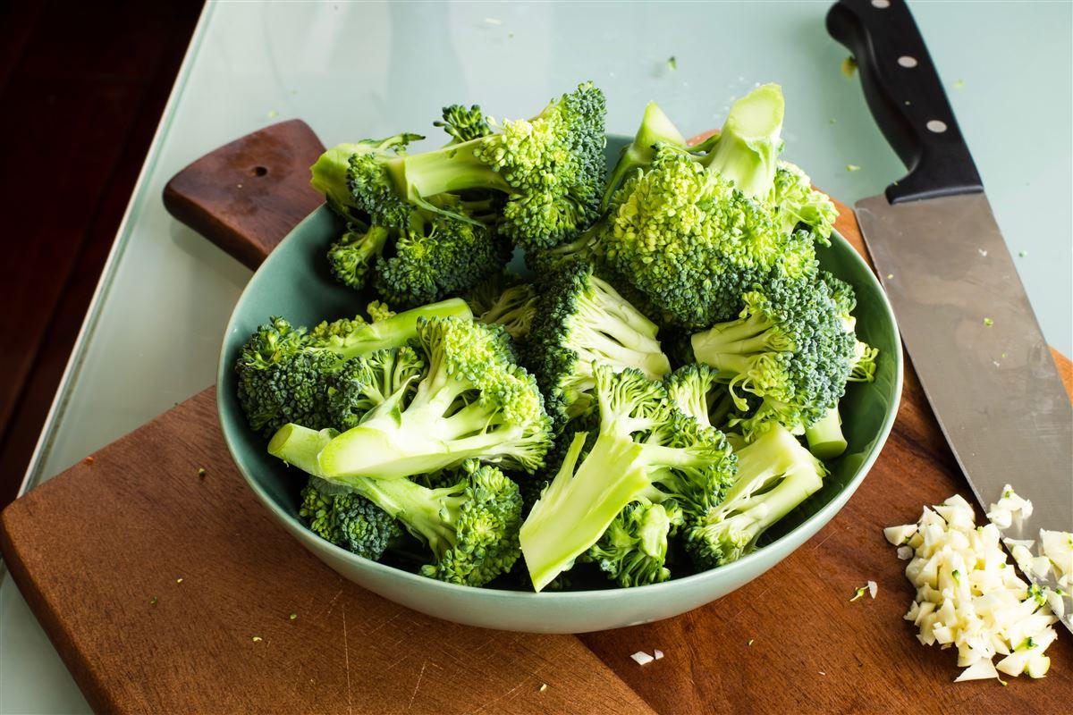 tallerken med broccoli står på et skærebræt