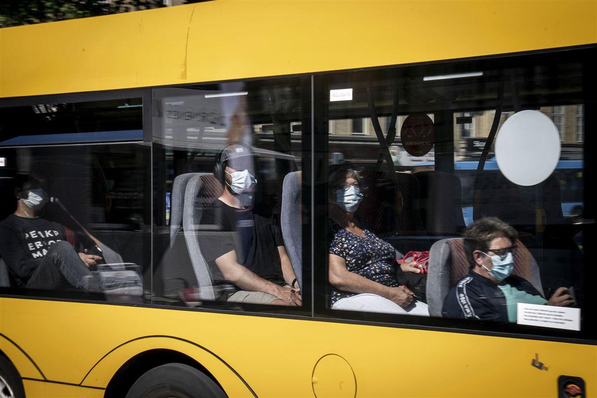folk med mundbind sidder i bus