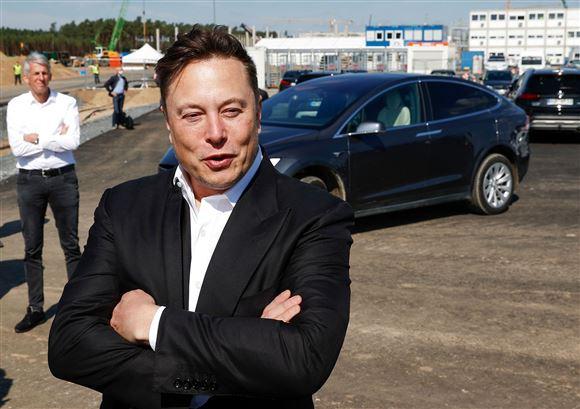 Elon Musk foran en Tesla
