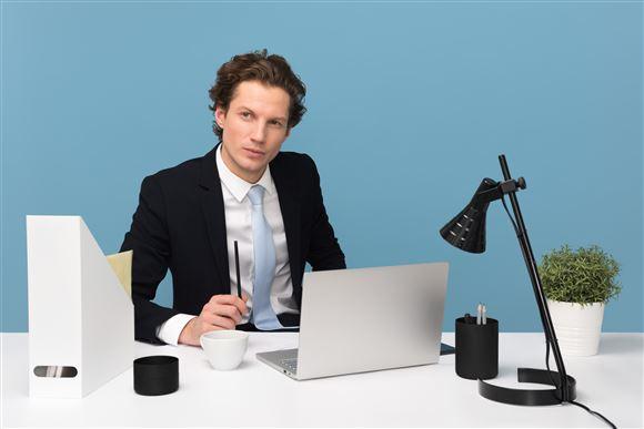Ungmand med slips ved skrivebord og computer
