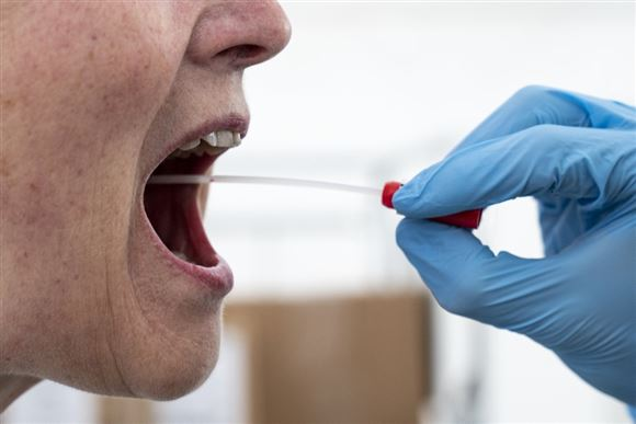 mand testes for corona med podepind i munden