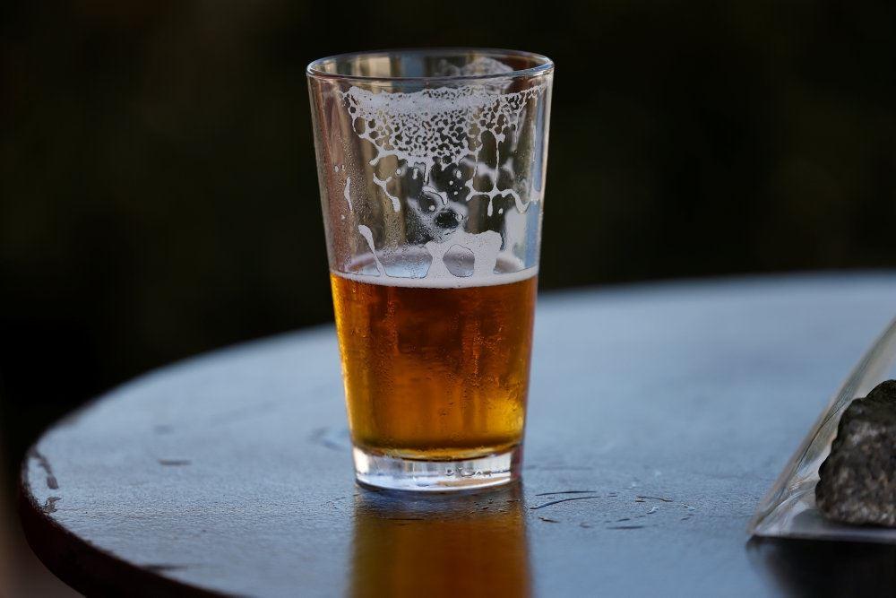 Et halvfyldt glas øl på et bord