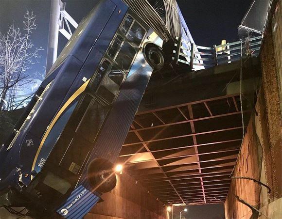 forreste del af en tandembus hænger og dingler ud over en bro i New York