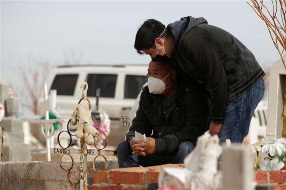 To sørgende mennesker på en kirkegård