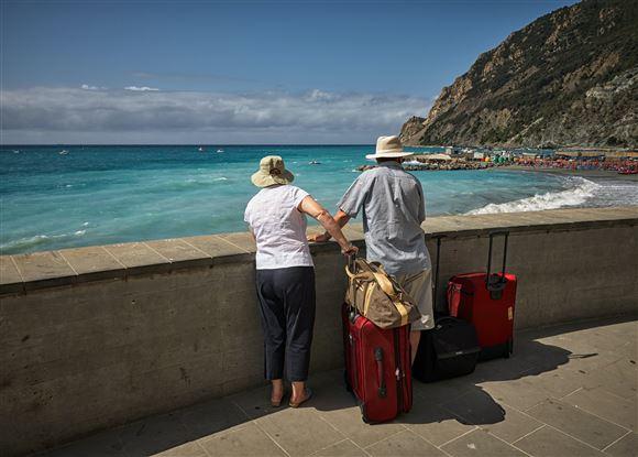 Et ældre par med kufferter kigger ud over en strand