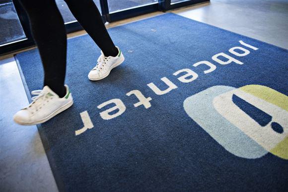 En person går på et gulvtæppe med jobcenter-logo